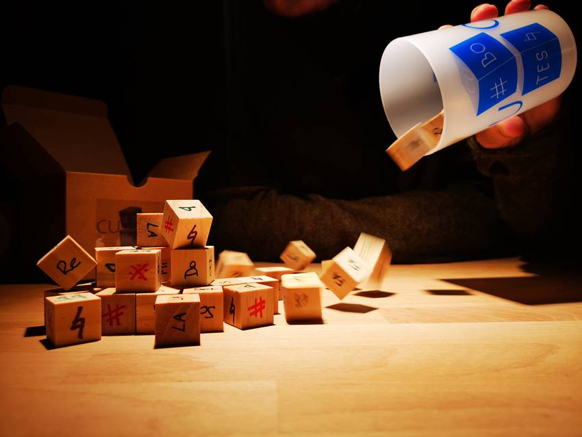 Los dados y el vaso que forman el juego Cubotes.